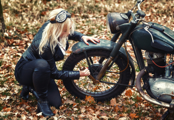 Woman tightens motorcycle axle