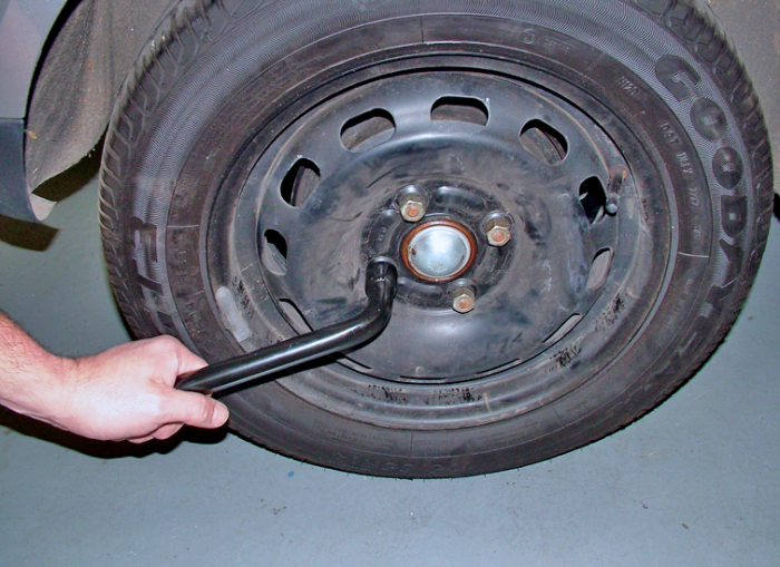 Loosen (but don't remove) the nuts or bolts with the wheel brace