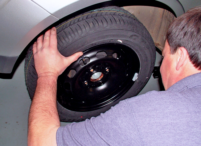 Fit the spare wheel, tightening the nuts or bolts by hand