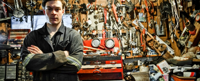 Mechanic stands in messy workshop