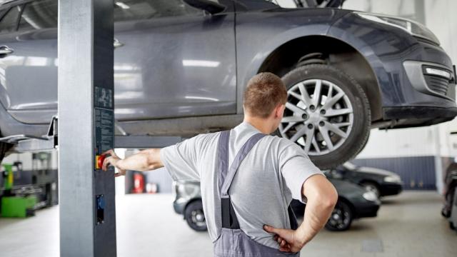 mechanic puts car up on lift