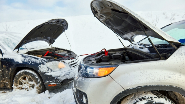 two cars in the snow with jumper cables