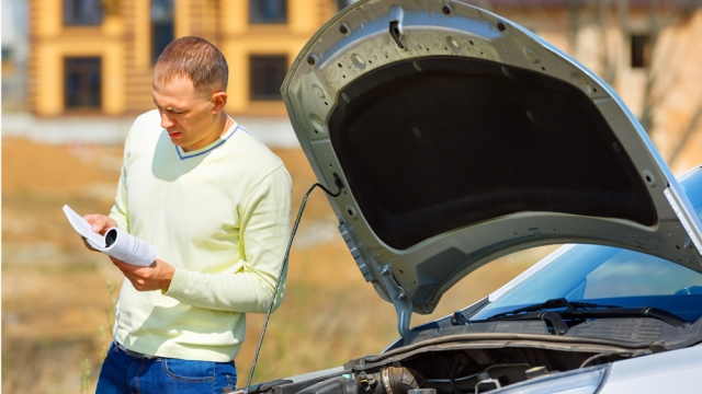Man looking for answers next to broken car