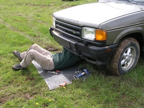shade tree mechanic working under car