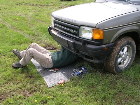 working under car in field