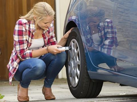 Woman checks her tire pressure