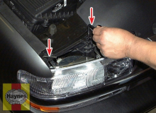 Twist the headlight housing mounting rod(s) (arrows) out of their clips and pull them straight up to disengage the housings