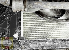 The drain fitting is located at the lower corner of the radiator