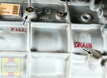 The manual transmission fill plug and drain plug are located on the side of the transmission case