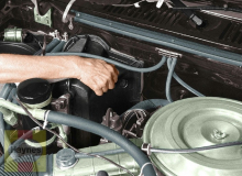 The automatic transmission fluid dipstick is near the firewall, to the left of the engine