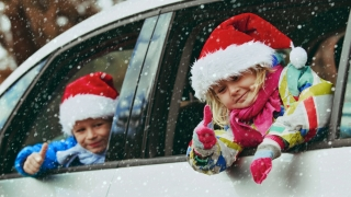 Kids in Christmas Hats in snowy car