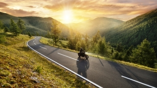 Motorcycle and rider cruise a mountain pass