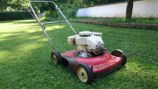 Old Lawn Mower on green lawn